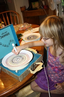 kid drawing with a purple marker on a paper plate that sits on a record player