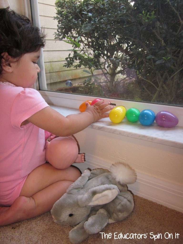 Toddler plying with Easter eggs putting in rainbow order