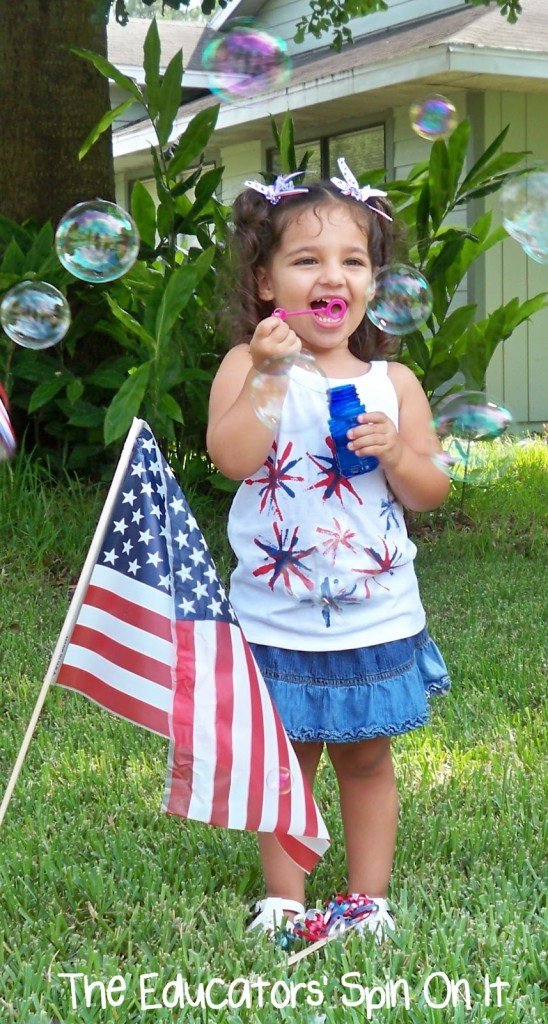 Child blowing bubbles near flag for Memorial Day