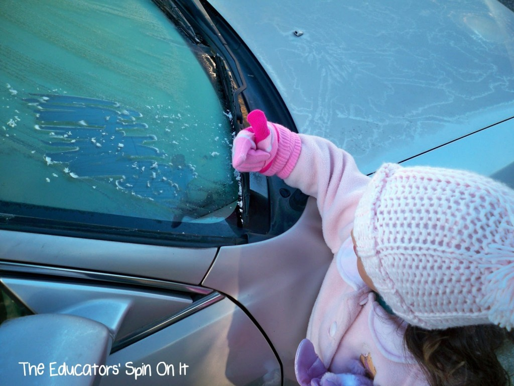 signs of winter frost on car with child scraping windshield