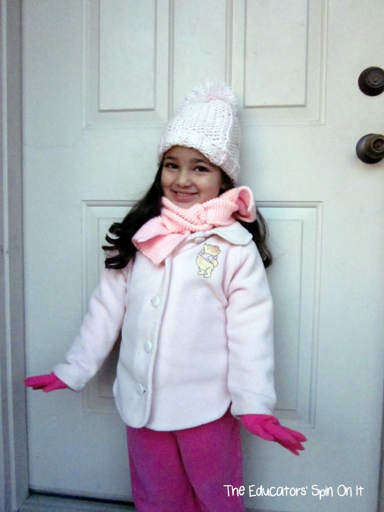 Learning about Winter Clothes with kids, a child in pink winter jacket with scarf and gloves.