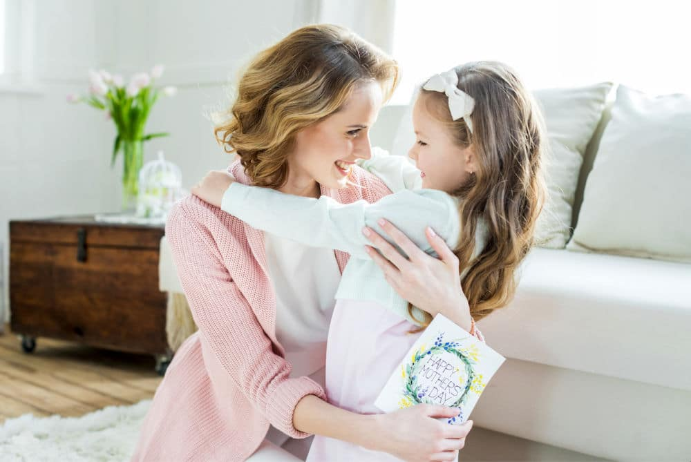 Mother and daughter with mothers day card hugging