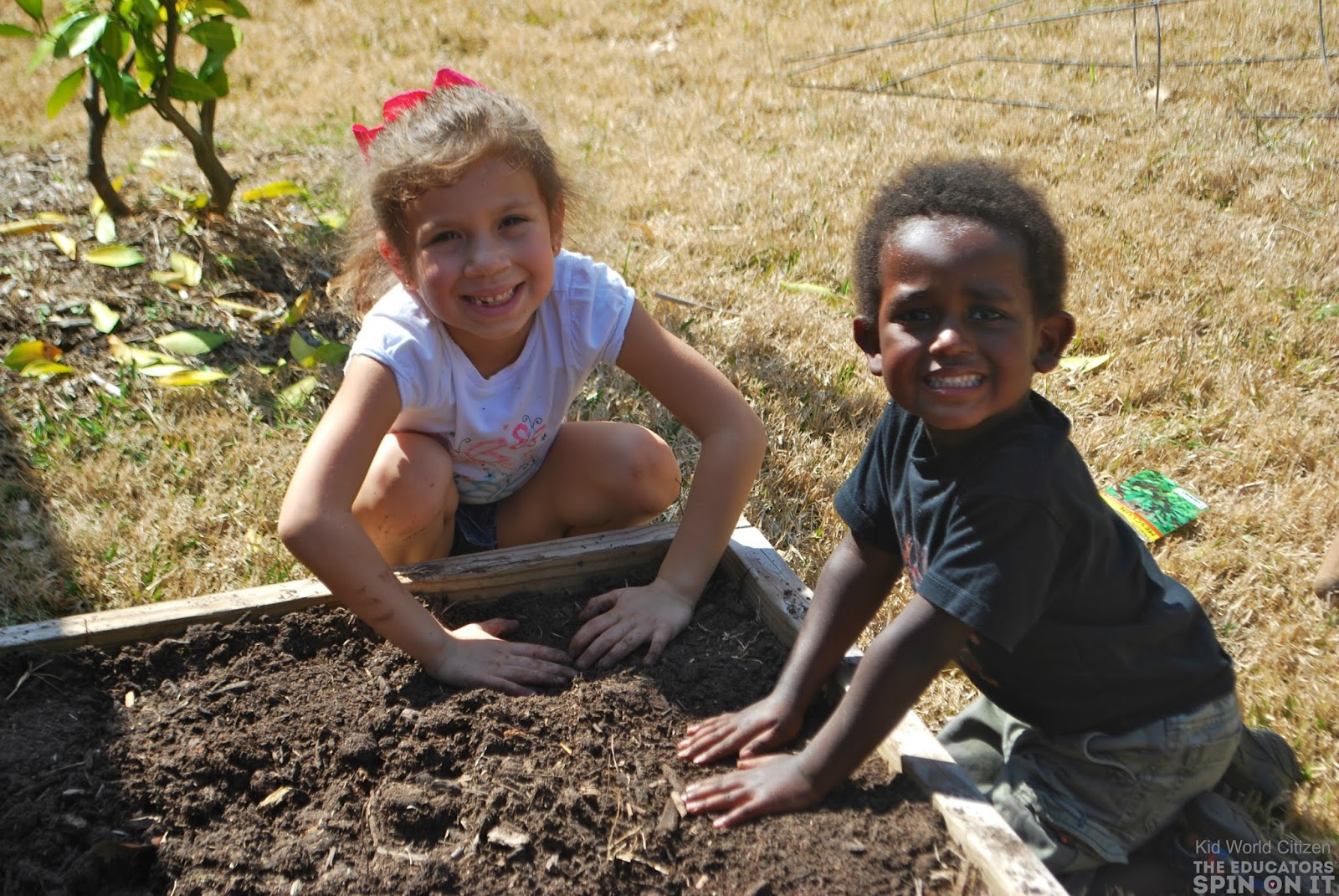 Two little gardners can't wait to plant vegetables in their backyard garden