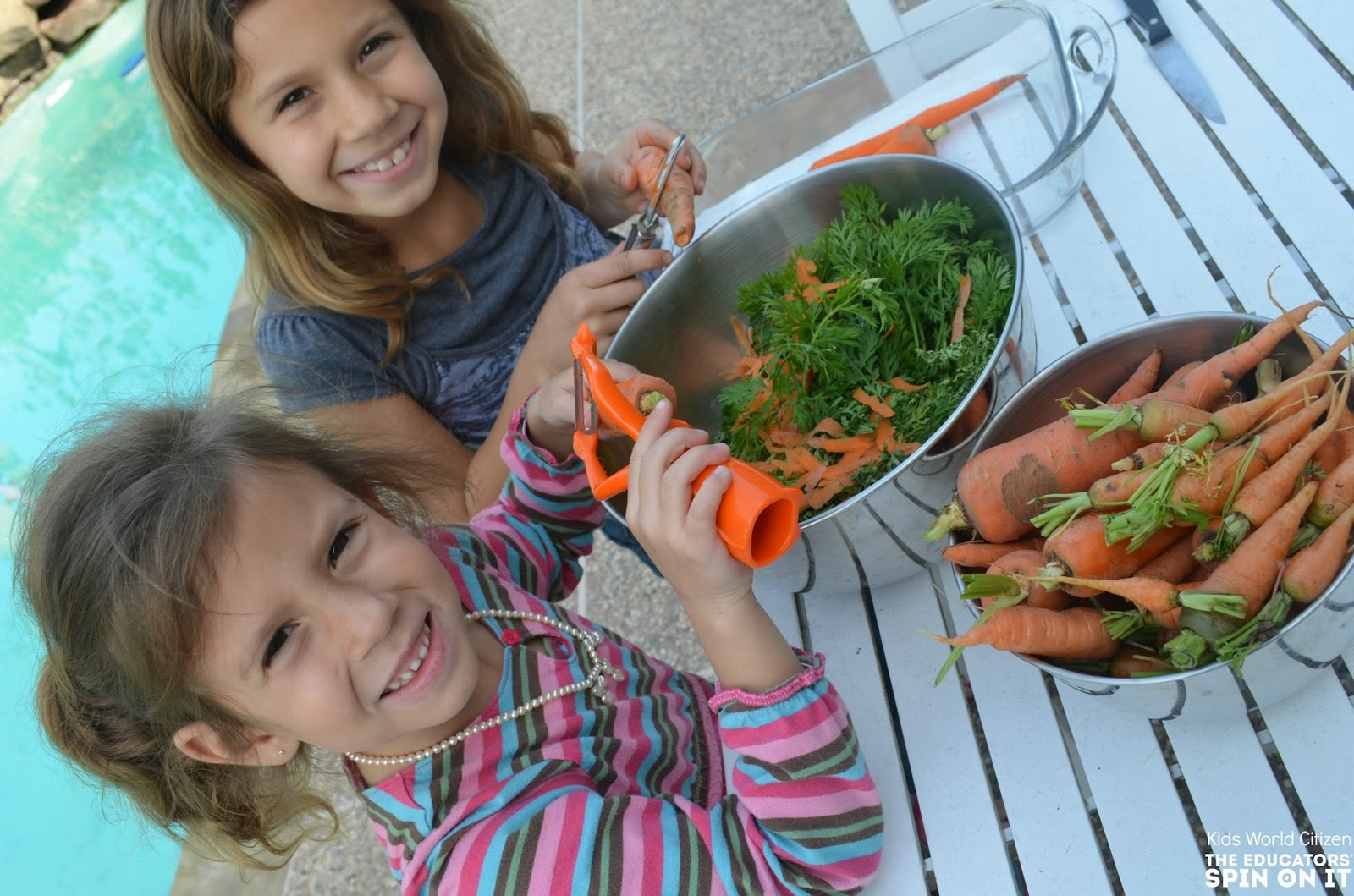 2 girls peel their carrot harvest from the garden.