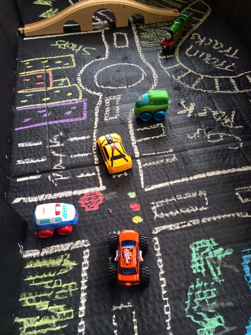 Chalk drawn town with roads in cardboard box and toy cars.