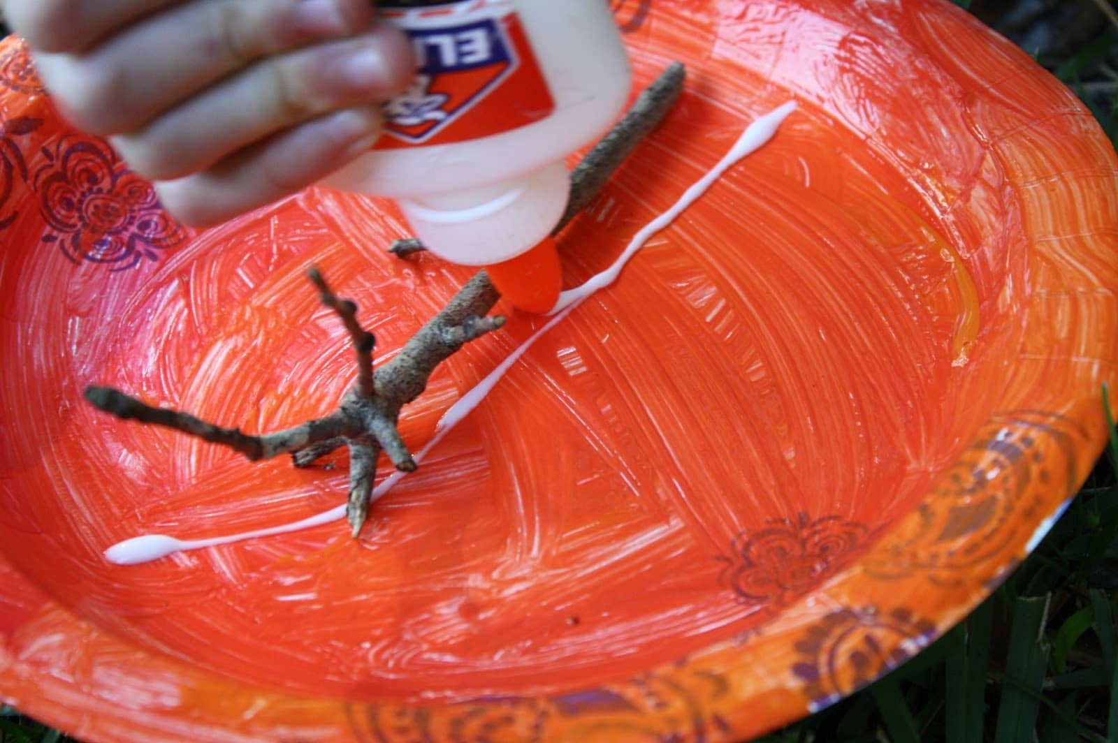 Glue a small branch or twig on to the paper plate to create the main tree trunk.