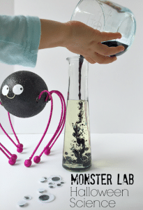 Glass Science beaker with child pouring mixture into with Googly Eyes and Black Spider watching