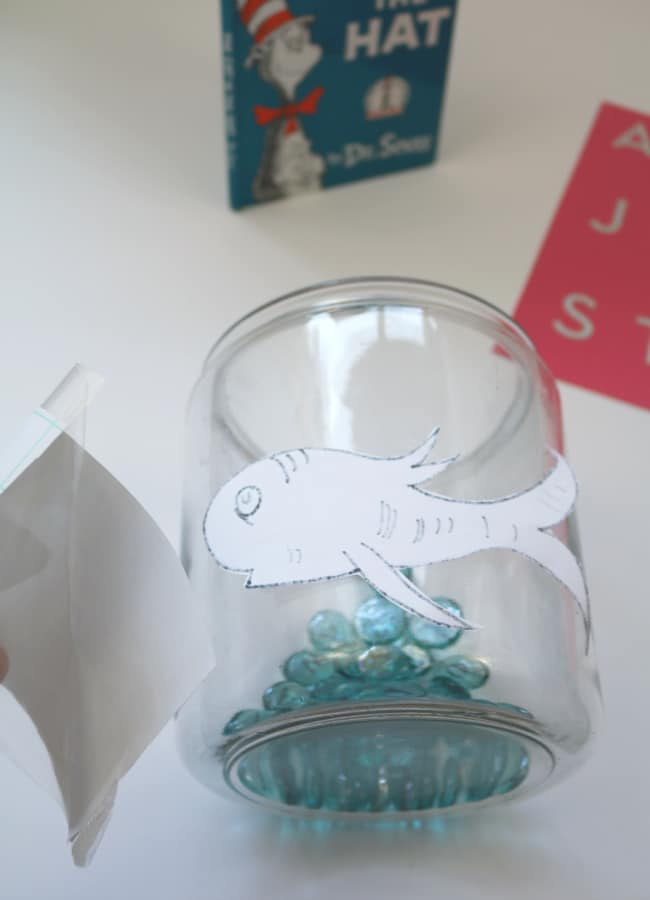Large fishbowl with Dr. Seuss inspired fish being attaching with contact paper