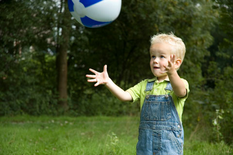 small boy playing with a ball outside