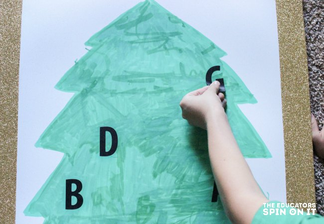 Adding letters to the tree to make Christmas Tree Alphabet Recognition Activity for Kids