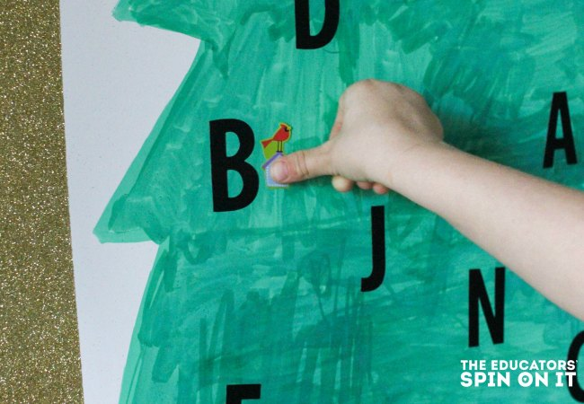 Putting letters on the tree for the Christmas Tree Alphabet Recognition Activity for Kids