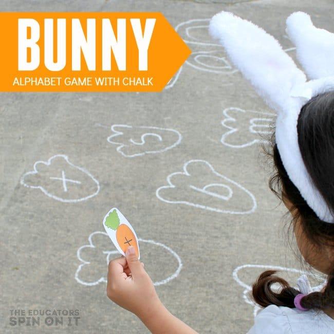 child holding paper carrot with letter looking for rabbit foot print with sidewalk chalk outdoors.
