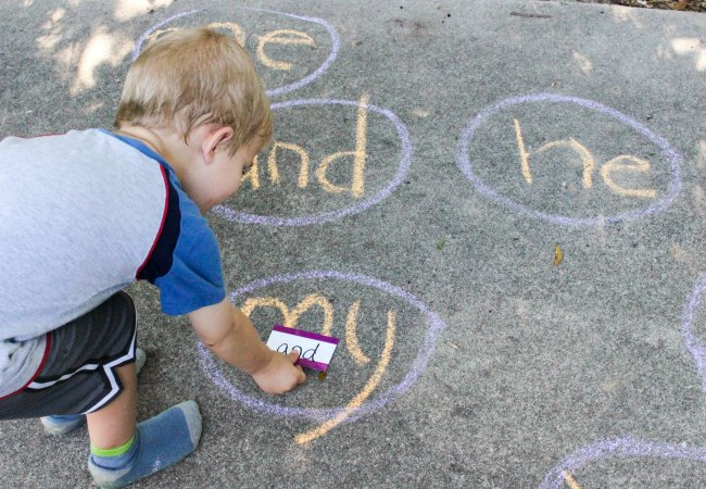 Child learning to read sight words while playing a sidewalk chalk sight word game