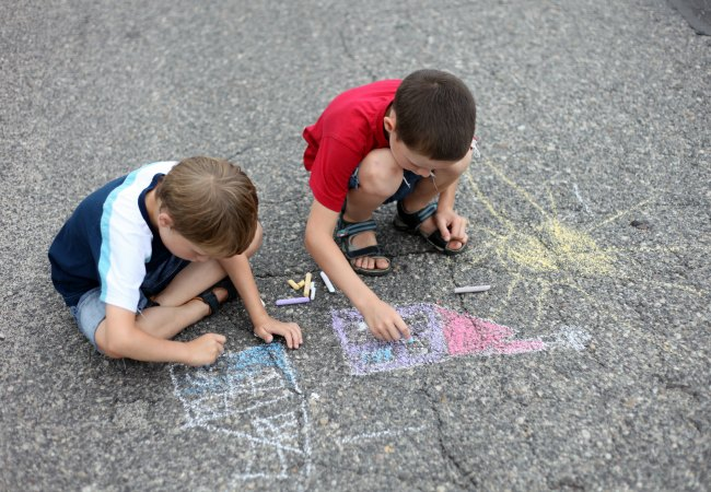 2 boys playing with sidewalk chalk