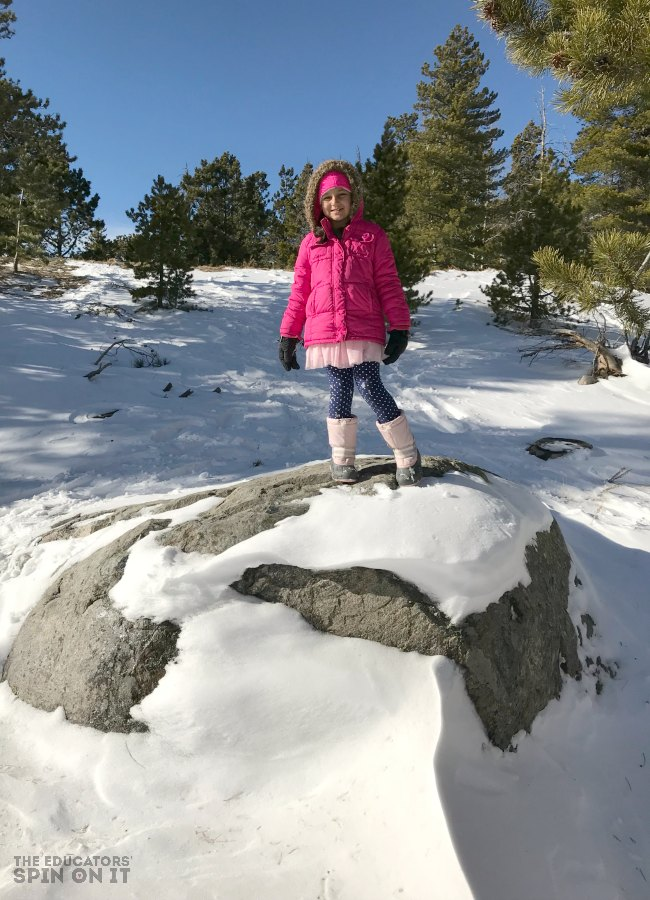 Hiking at Bear Lake in the Rocky Mountain National Park with snow covered boulder and young child.