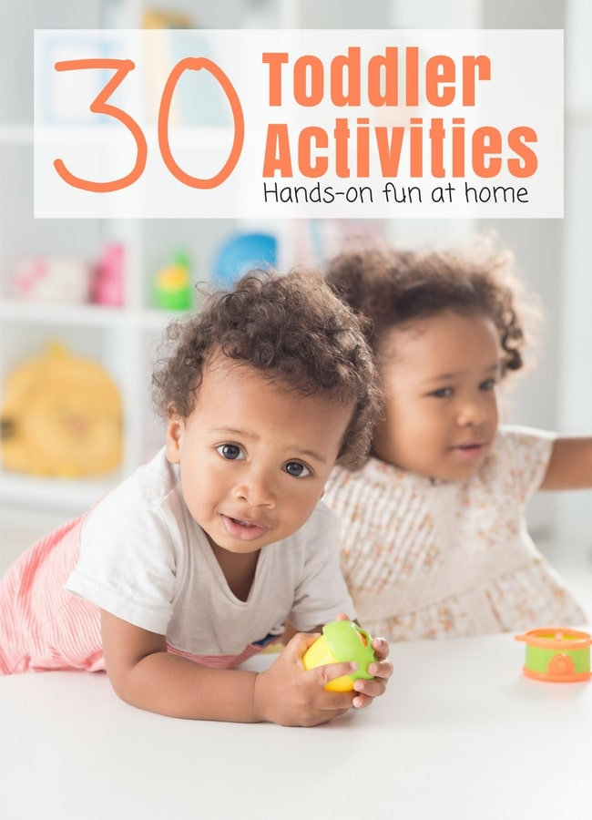 2 Toddlers Playing at White Table with Toddler Toys on Bookcase