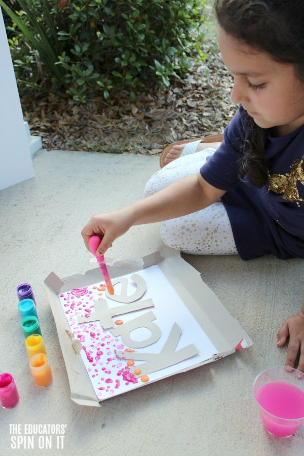Child drip painting with rainbow colored paints onto paper with stenciled name