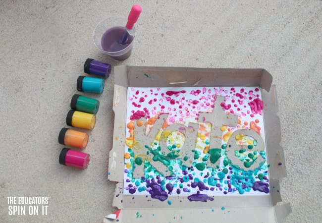 Paint dripped onto letters of name with rainbow colored jars and dropper