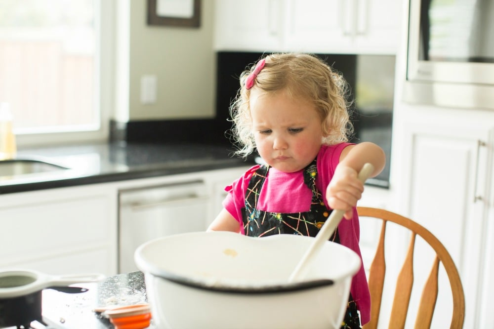 Toddler in Virtual Book Club Summer Camp doing Cooking Activity in Kitchen with large mixing bowl and spoon