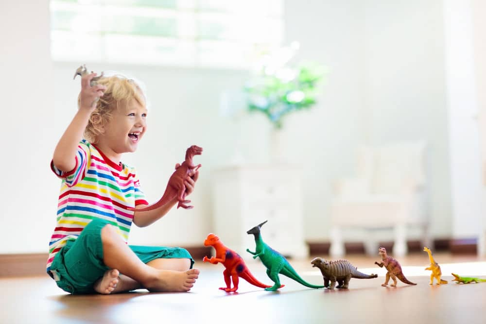 Young child playing with pretend dinosaurs