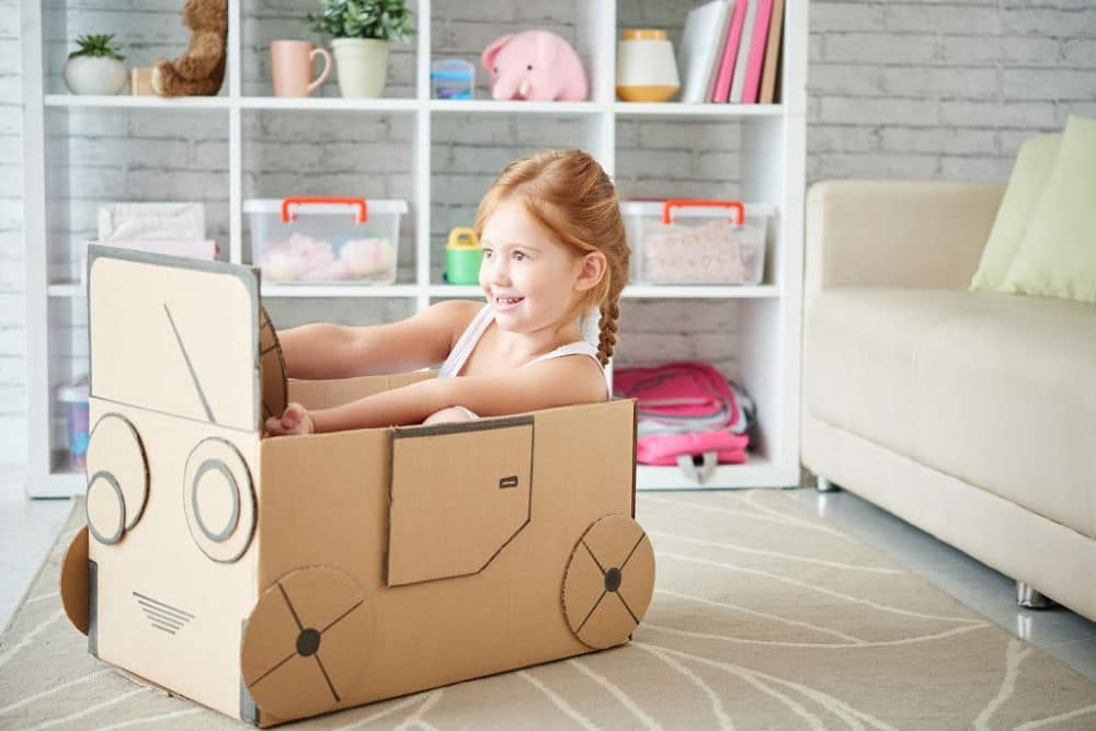 Cardboard Car with girl inside pretending to drive