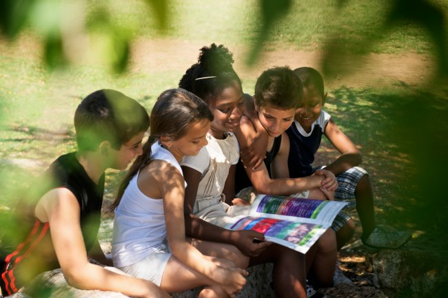 Children Reading together under tree