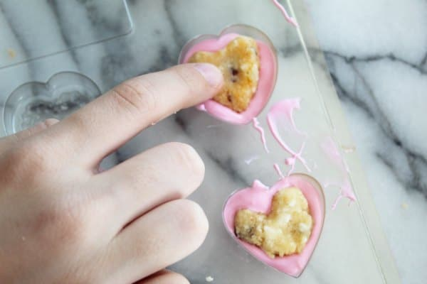Making Candy Heart by placing cake into heart form with melted candy chocolate