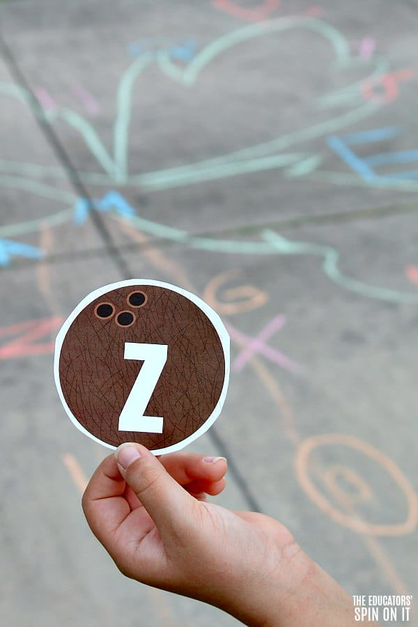 Child holding pretend coconut with the letter Z to play sidewalk chalk game inspired by Chicka Chicka Boom Boom