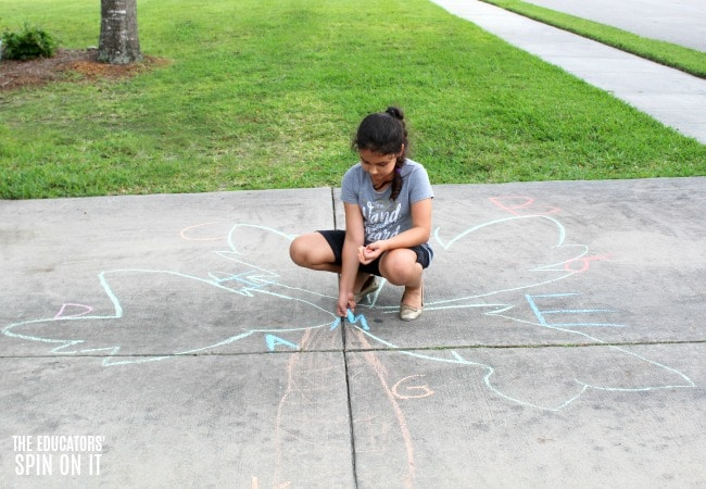 Child writing letters with sidewalk chalk onto Chicka Chicka Boom Boom book inspired Coconut Tree.