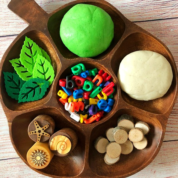 green and white playdough on wooden tray with letter, wood and felt leave to make coconut tree