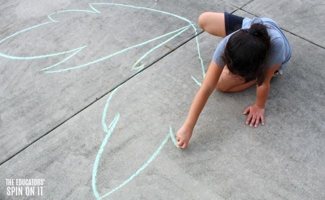 Child making palm frawns with green sidewalk chalk