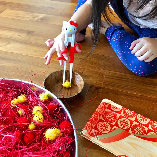 Young girls learning to use chopsticks with red and yellow pom poms in silver bowl