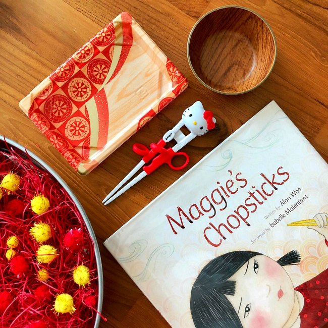 Maggie's Chopsticks book with practice chopsticks and red and yellow pom poms in silver bowl