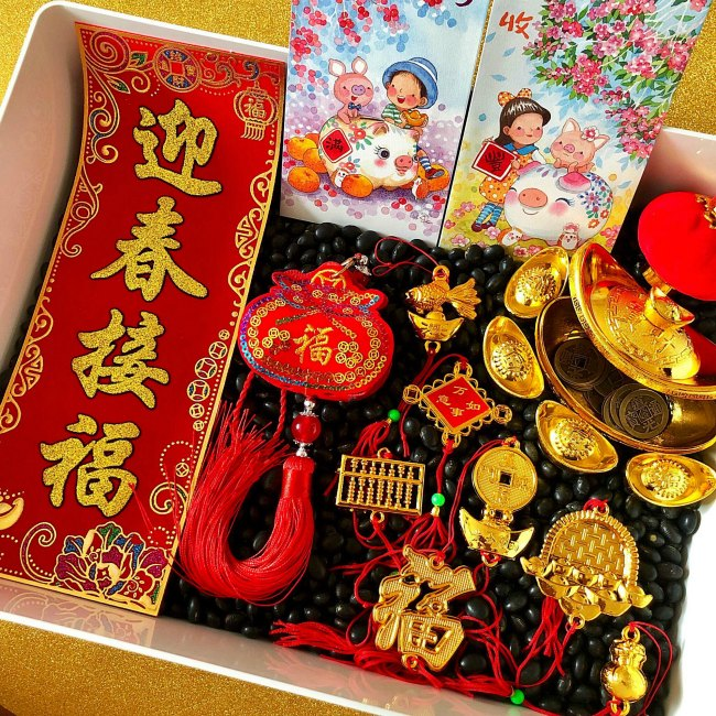 Chinese New Year Sensory Bin with Black Beans and Golden items and red envelope
