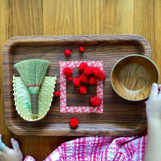 Young girl using small broom on wooden tray for Chinese New Year Activity