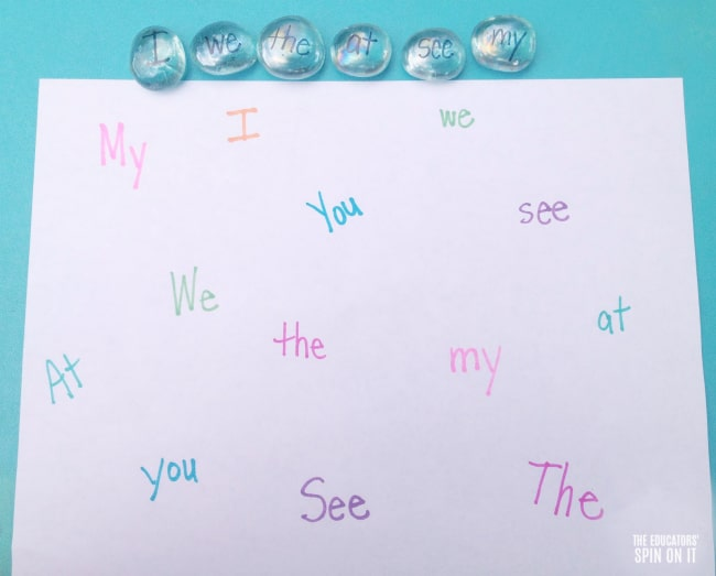 Glass gems with sight words written on them to create a matching game on paper for beginning readers.