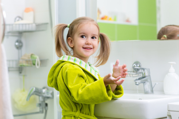 Child learning how to wash their hands