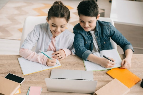 siblings working on school work at home at table with laptop, paper and pencils