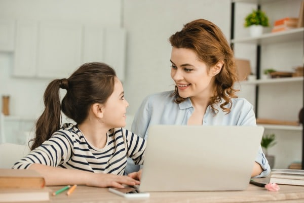 parent working from home with child sitting next to them at table