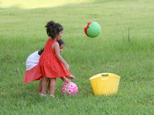 two girls tossing balls into yellow bucket in backyard