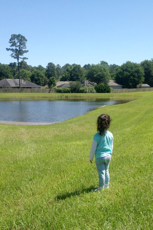 girl standing in grass in backyard looking at retention pond in grassy field