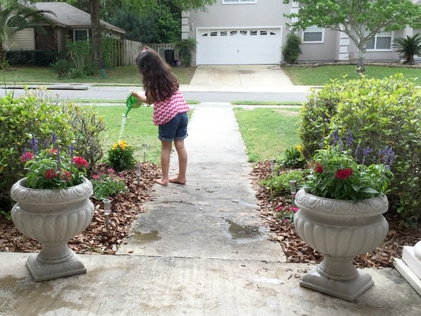 girl watering plants at front yard for butterfly garden