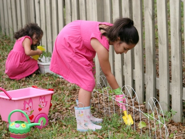 two girls gardening in backyard with gardening tools near fence