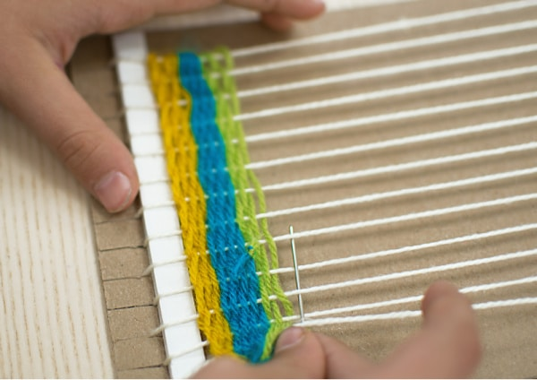 Teaching a child to learn to weave with cardboard loom and colorful yarn.