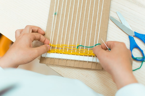teaching child to weaving with cardboard loom and yarn.