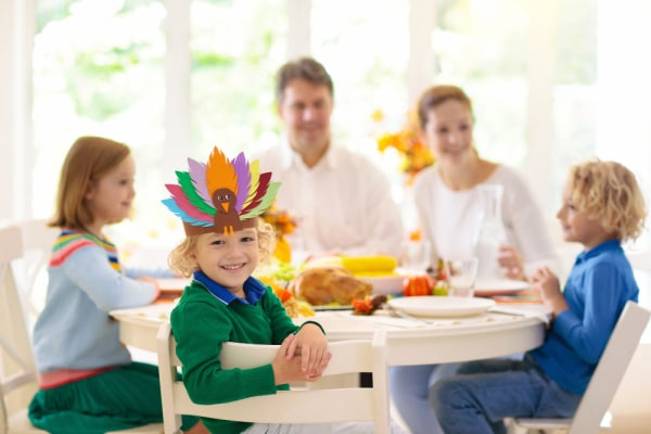 Family with kids eating Thanksgiving dinner. Roasted turkey and pumpkin pie on dining table with autumn decoration. Parents and children festive meal. Father and mother cutting meat. Paper turkey crafts hat.