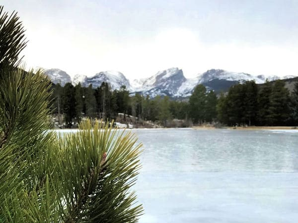 Frozen lake in Rocky mountains with mountains in backgroun