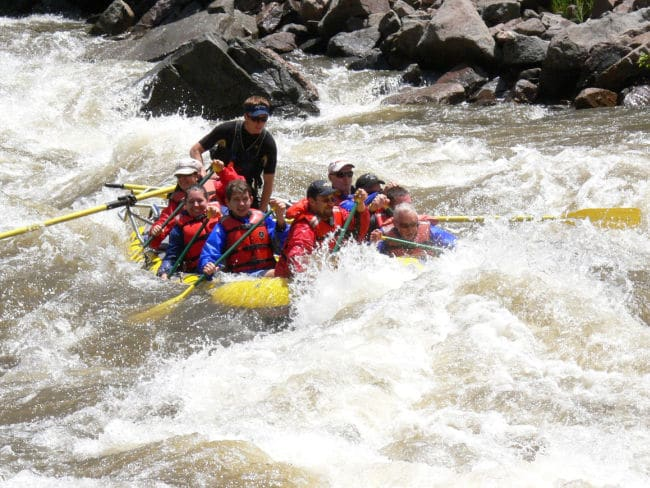 Large Group of people in vests rafting down the Colorado river with waves and rocks in background.